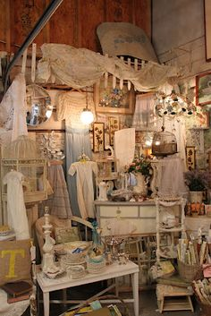 picket fence at top of booth display shabby beige theme, white furniture accessories.old sheet draped like a valance