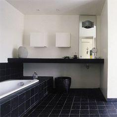 Salle de bains avec baignoire, plan de toilette, sol tapissés de carrelage en ardoise