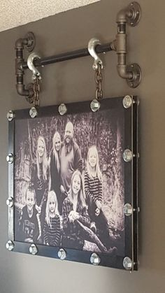 photo frame I made using plasma-cut plate steel. Used torch and gear lube to darken the steel. x hex bolts, washers and nuts to sandwich the canvas between the backing plate and the frame. chain and hooks to hang it from screw pipe and fittings.