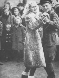 A Soviet soldier dances the polka with a blonde, befurred German girl in central Berlin during the Christmas holiday celebration. December 25, 1945
