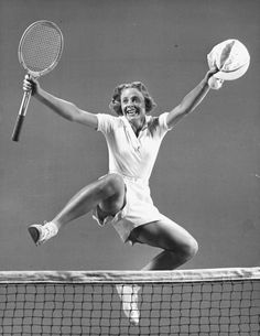 Alice Marble, 26, top US woman tennis player, victoriously leaping over the tennis net on court - 1939