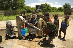 Children by a borehole drilled using Fairtrade premium funds in Kasinthula sugar cane co-operative, Malawi, © Annette Kay