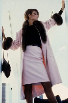 Carol Alt models a fur-trimmed coat Photo by Denis Piel Model Carol Alt wearing a pale pink skirt and matching coat with fur cuffs and collar. Circa July 1980