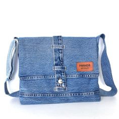 The fabric of this messenger bag was a denim pant in blue color before having a new life. I used part of pants waistband and formed a closure. I attached two original pockets on the back side of the bag. Adjustable strap, made from denim, offers custom-fit carrying. It is fully lined with cotton fabric,and features 2 interior pockets. This comfortable and sturdy messenger bag is ideal for carrying your every day items to work or your tablet and books to school.  Measurements: width:13.5…
