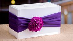 White card box with purple sash and hydrangea