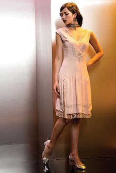 """If you're feeling fancy, try Queenie's whimsical flapper dress. Pay special attention to the embroidered design, which includes wands and the Legilimency emblem. 