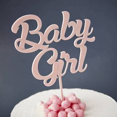 baby shower cake toppers girl, close up of a pale pink cake topper, reading baby girl, placed on a white cake, with pink decorations