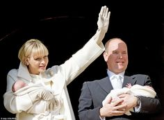 Glamorous: A white-gloved Princess Charlene beams at the crowd as a smiling Prince Albert looks on