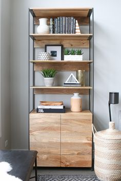 This bookshelf holds pretty items and accessories in this neutral living room space. How to style a bookshelf #bookcasestyling