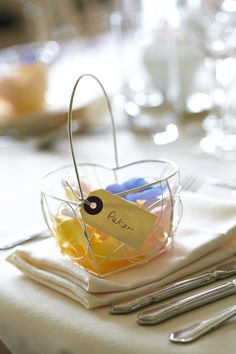 Heart wedding table decoration containing pastel yellow, blue and pink petals.