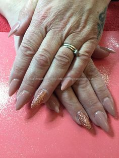 Acrylic nails almond shaped with rose gold glitter on ring fingers