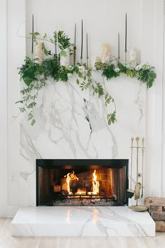 Marble fireplace with vines and foraged foliage and Mexican onyx hurricanes. DIY by Alicia Rico, bows + arrows flowers. Photography by Apryl Ann.