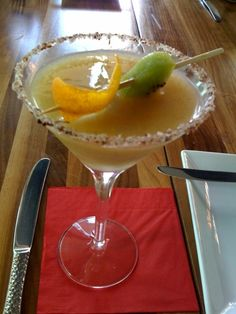 Mezcal Cocktail with candied orange peel, kiwi, fruit puree and a chili powder / sugar rim