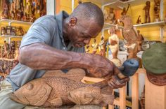 Local wood carver at the Straw Market in the Bahamas http://www.bahamasfinder.com/the-straw-market.html