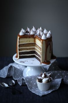 layers of dark chocolate, caramel and white chocolate cakes encased in a velvety smooth salted caramel swiss meringue buttercream dripping with homemade creamy salted caramel sauce and topped with crispy sweet chocolate swirl meringue kisses.