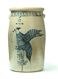 """RARE OHIO STONEWARE CHURN.  Summit County, Ohio, 1865-1880. Six-gallon of typical form, decorated in cobalt with an elaborate bird on a branch, holding in its beak a banner reading """"Akron, Ohio' and under the name """"D.S. Alexander.' Imperfections"""