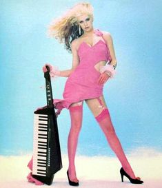 Keytar aaarrggghhh -- So 80's.  But, it's one of the few times a beautiful woman is shown next to a synth, as opposed to a guitar, even if it's a Keytar.