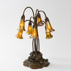 "A Tiffany Studios New York ""Seven-light Lily"" Favrile glass and patinated bronze table lamp. The lamp features seven golden Favrile glass ""Lily"" shades suspended above a patinated bronze ""Lily Pad"" base."