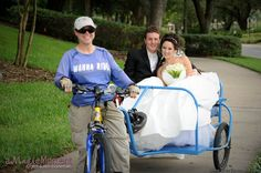 Newlyweds take a ride through the park in a blue bicycle taxi, or pedicab, on their wedding day. The bride's voluminous ballgown barely fits inside the small cab, and bits of tulle peak out from under the satin skirt. A crystal tiara adorns her dark curls and she holds a bouquet of white calla lilies. The fun-loving couple held their wedding and reception at The Peabody Hotel. The John Parker Band kept the guests dancing all night long! http://www.jpband.com/weddings.html