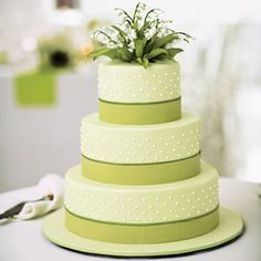 Ribbon and Dots. This wedding cake was decorated with clean and simple Swiss dots and green fondant grosgrain ribbon, topped with lily of the valley. Each of the three tiers had a different flavor combo: vanilla and cookies and cream; chocolate peanut butter and raspberry preserves; and citrus cake with blood orange and vanilla buttercream.
