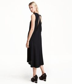 Sleeveless dress in a crêpe weave with cut-out sections at the back, a hook-and-eye fastener at the back of the neck and a skirt that is in a double layer at the back with a high slit in the top layer. Partly lined.