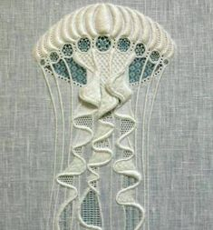 The Tentacle Whitework needlepoint jellyfish by apprentice Lucy Reed, at the Royal School of Needlework.  Whitework: The term apples to a variety of techniques ranging from the bold stitches of Mountmellick and Hardanger to the delicate work of Ayrshire and Fine White embroidery. Traditionally worked with white thread on white fabric and used for bridal and christening wear and ecclesiastical embroidery.  How elegant!  http://www.royal-needlework.org.uk/galleries/images/25/