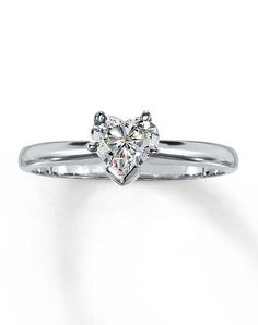 Stunning Heart shaped diamond solitaire shines from the center of this engagement ring set in stunning