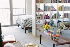 Una biblioteca sin fondo aísla el área del dormitorio y otorga espacio de guardado