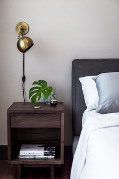In one of the guest bedrooms, smart choices like a Room & Board bed and side table and stylish Schoolhouse Electric brass sconce maintain the residential aesthetic on a more moderate budget.