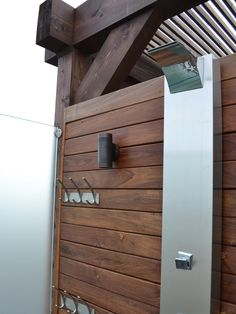 A contemporary stainless steel fixture and frosted glass enclosure makes this outdoor shower refined enough to live inside the house. A adjacent dressing area adds convenience and function.