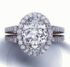 Oval diamond with diamond halo with double diamond split shank engagement ring in white gold