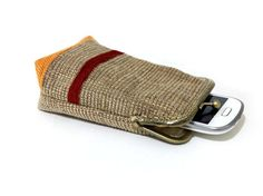 This fabric Smartphone Case / Cigarette Case is very chic.  You can use this case for a smartphone, cigarettes, Digital camera, and more. Beautiful, sophisticated and unique, this case is perfect for every woman, Holding your keys, credit cards, lipstick, ID, money, etc. Inside the case you have an open pocket for the cards.  The case is made of Beige/ light brown Upholstery fabric with lovely strips in orange and deep red and interior beige cotton fabric. A layer of cotton is padded in…
