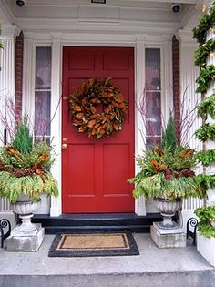 love magnolia leaves front entrance... Maybe copper buckets or barrels instead of concrete planters