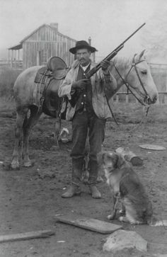 A man with his horse, gun and dog. Some men have it all.
