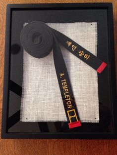 Black belt shadow box - taekwondo. A simple way to show both ends of the belt. Used a black shadow box and a piece of burlap. Everything is secured with straight pins.
