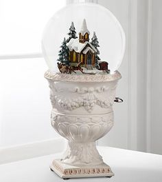 """Christmas Village Church Snow Globe by San Francisco Music Box Company. The Christmas Village Church Snow Globe by San Francisco Music Box Company is a holiday gift that they will cherish each winter season! Set on a white urn-shaped base intricately displaying grape and leaf accents, this snow globe displays a village church scene with a carriage rotating around it for an incredible effect. Featuring the time-honored tune, """"Silver Bells"""", this music box is set to enchant friends, family and…"""