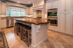 Kitchen with custom cabinetry, center island with cherry wood top and desk area in this home in Chatham NJ