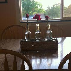 Empty wine bottles as flower vase centerpiece.