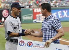 Former Texas Rangers player Michael Young greets New York Yankees shortstop Derek Jeter (2) during a pre game ceremony honoring Jeter before a game between the Texas Rangers and New York Yankees at Globe Life Park in Arlington on Wednesday, July 30, 2014.  (Vernon Bryant/The Dallas Morning News)