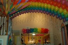 The arches are individual single balloon arches made from fishing line and 22 balloons tied directly on them about 12 inches apart. I added the ribbons to make the effect even bigger. The lines are anchored at the top of the stairs along the wall vertically on 3m hooks and anchored with big rocks horizontally on the top of the desk. The rocks are covered by air-inflated white balloons for clouds.