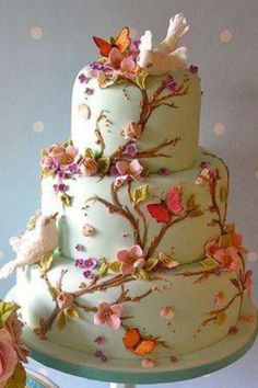 Pale green 3-tier cake decorated in branches and flowers.