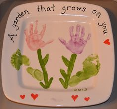 """This one is a spring/garden picture on a square charger plate that I made with my 22 month old's hand and foot prints.  I made the """"flowers"""" with my child's handprints and used their footprints for the """"leaves.""""  I also painted my child's name along the bottom between the hearts (I blurred it for privacy.)"""