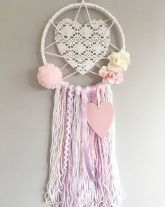 This •Sweetheart Lace Dreamcatcher• has been made using a 6 inch hoop. The tassels measure around 30/40cm long and have been created using a mixture of ribbons and yarn. The pompoms and tassels have also been handmade. Would look beautiful in a little girls bedroom. •Please note -