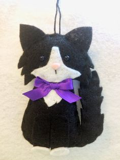 This beautiful black cat makes a sweet gift for anyone who loves cats. Personalize this kitty to make a wonderful memorial of a beloved pet. This sweet ornament is designed and handmade by me. It is made of black and white felt and is adorned with a purple bow. It is about 4 1/2