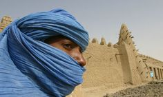 A Tuareg nomad stands near the 13th century mosque at Timbuktu in Mali.