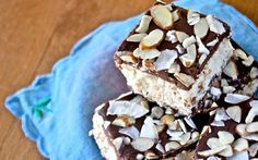 <p>A fluffy, coconut center is sandwiched between a chocolatey walnut-date crust, and then topped with a layer of smooth, rich dark chocolate ganache. A sprinkling of toasted sliced almonds and flaked coconut adds a finishing touch.</p>