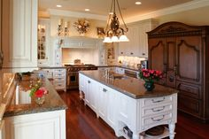 An English country and French country fusion with a massive dark wood china cabinet. The rest of the kitchen is in pristine white with delicate, subtle carved details. The room is accented with white pottery and a series of floral arrangements in various vases.