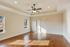Master bedroom with gleaming hardwood flooring and a stepped ceiling.