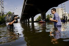 Bangkok, Thailand: A television journalist reports in floodwaters outside Don Muang airport