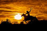 Cowboy Riding Horse at Sunset on Hill